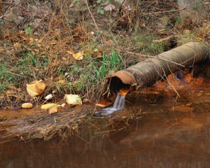 Rusted Pipe Draining into Polluted Water